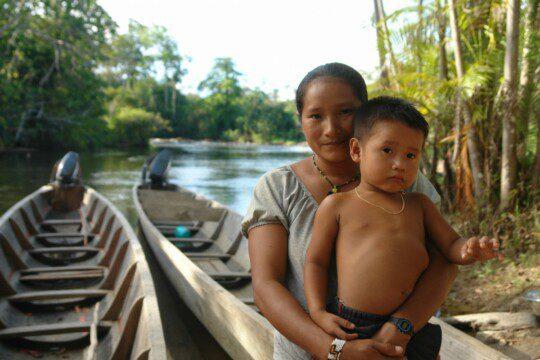 Eine indigene Frau und ein Mächen auf einem Kanu
