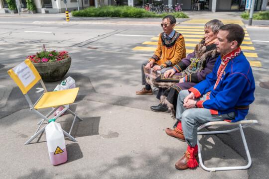 Drei Indigene sitzen auf Stühlen