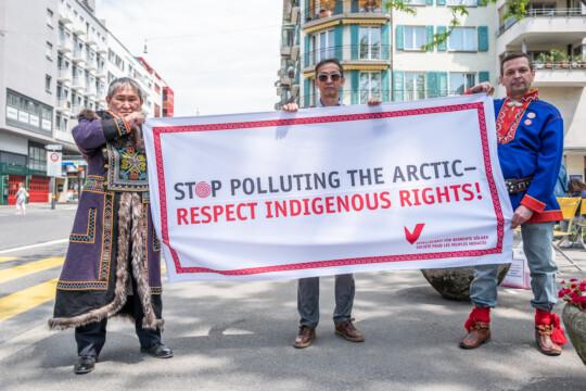 Drei Indigene halten ein Plakat