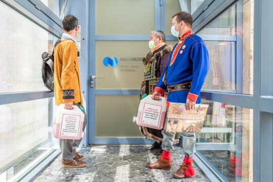 Drei Indigene stehen vor einer Tür