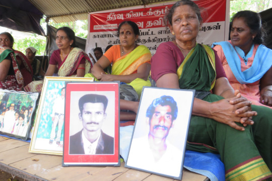 Tamil women show pictures of forcefully disappeared family members at a protest in Sri Lanka.
