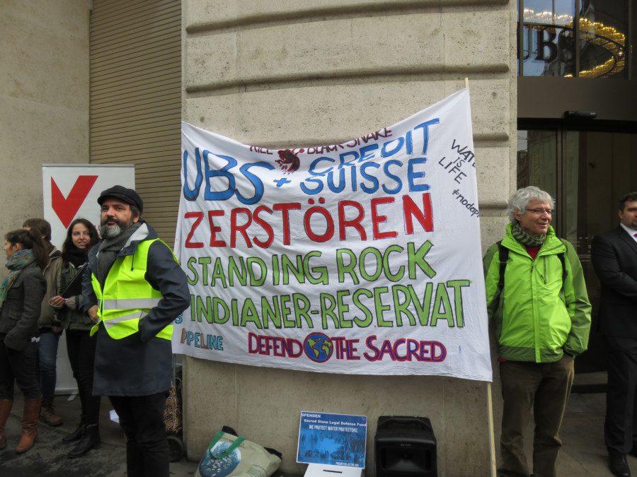 Aktivisten stehen neben einem selbstgemachten Banner an einer Standing Rock-Demonstration in Basel.