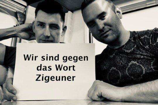 """Zwei Roma-Vertreter halten Plakat """"Wir sind gegen das Wort Zigeuner"""""""