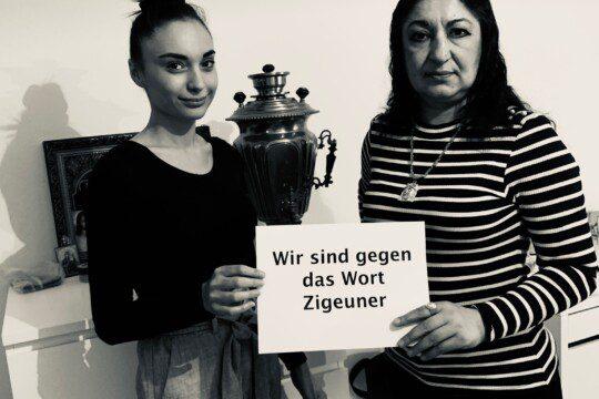 """Des représentantes roms tiennent une affiche: """"""""Wir sind gegen das Wort Zigeuner"""""""