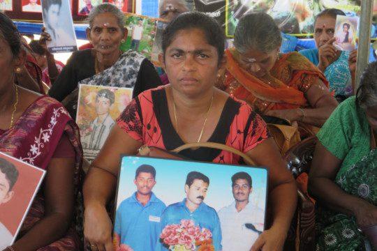 Sri Lanka: Eine Tamilin hebt Fotos von verschwundenen Angehörigen vor die Kamera.