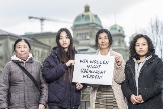 """Tibeterinnen in der Schweiz mit Plakat """"Wir wollen nicht überwacht werden!"""""""