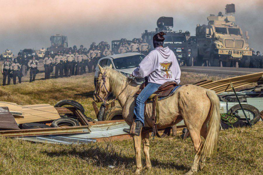 Ein indigener Aktivist auf einem Pferd stellt sich gegenüber der amerikanischen Polizei. bei eine Auseinandersetzung in Standing Rock.