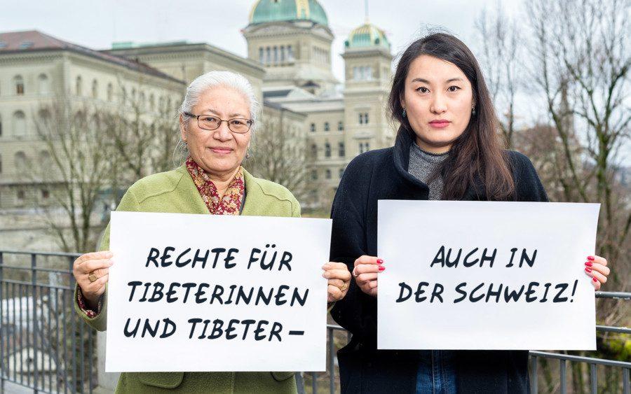 Zwei tibetische Aktivistinnen halten vor dem Bundeshaus ein Schild.