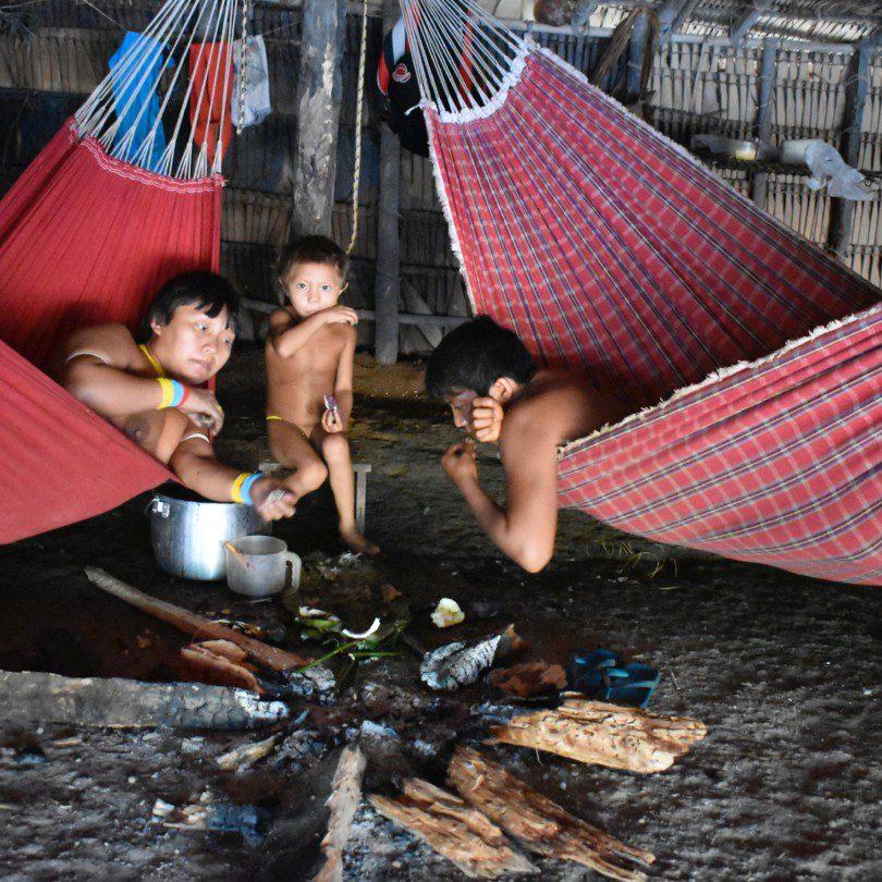 Junge Yanomami auf Hängematten essen um ein Holzfeuer.